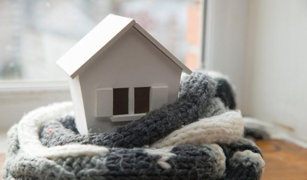 Model budynku w szaliku jako symbol termomodernizacji domu